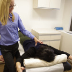 Manual and verbal cues help a patient with neck pain.